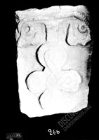 Stone with image of twisted cross on base shaped like scrolls or roots