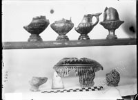 Below, shard of VESSEL of unclear shape, shoulder of fluted oinochoe decorated with eggs applied by thin clay and scratching, aryballos without neck